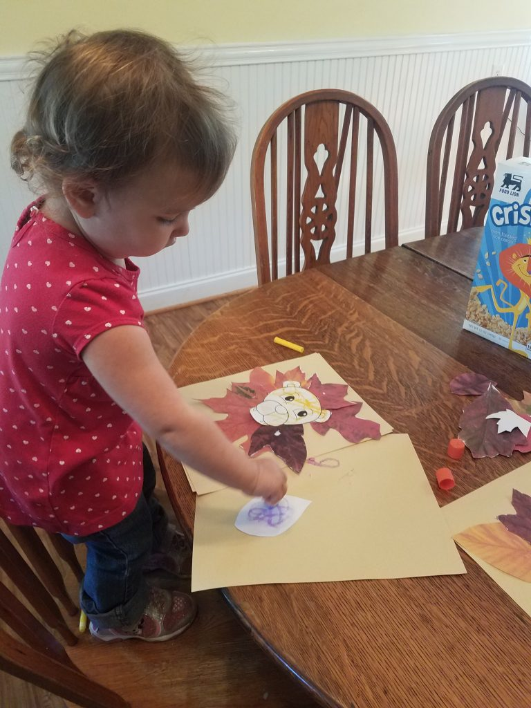 child gluing on art project